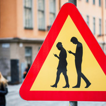 TOPSHOT - A road sign arning against pedestrians focusing on their smartphones is pictured on February 2, 2016 near the old town in Stockholm. / AFP / JONATHAN NACKSTRAND