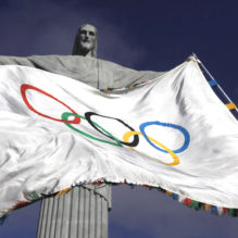 """The Olympic Flag flies in front of """"Christ the Redeemer"""" statue during a blessing ceremony in Rio de Janeiro August 19, 2012.  REUTERS/Ricardo Moraes (BRAZIL - Tags: SPORT OLYMPICS RELIGION)"""